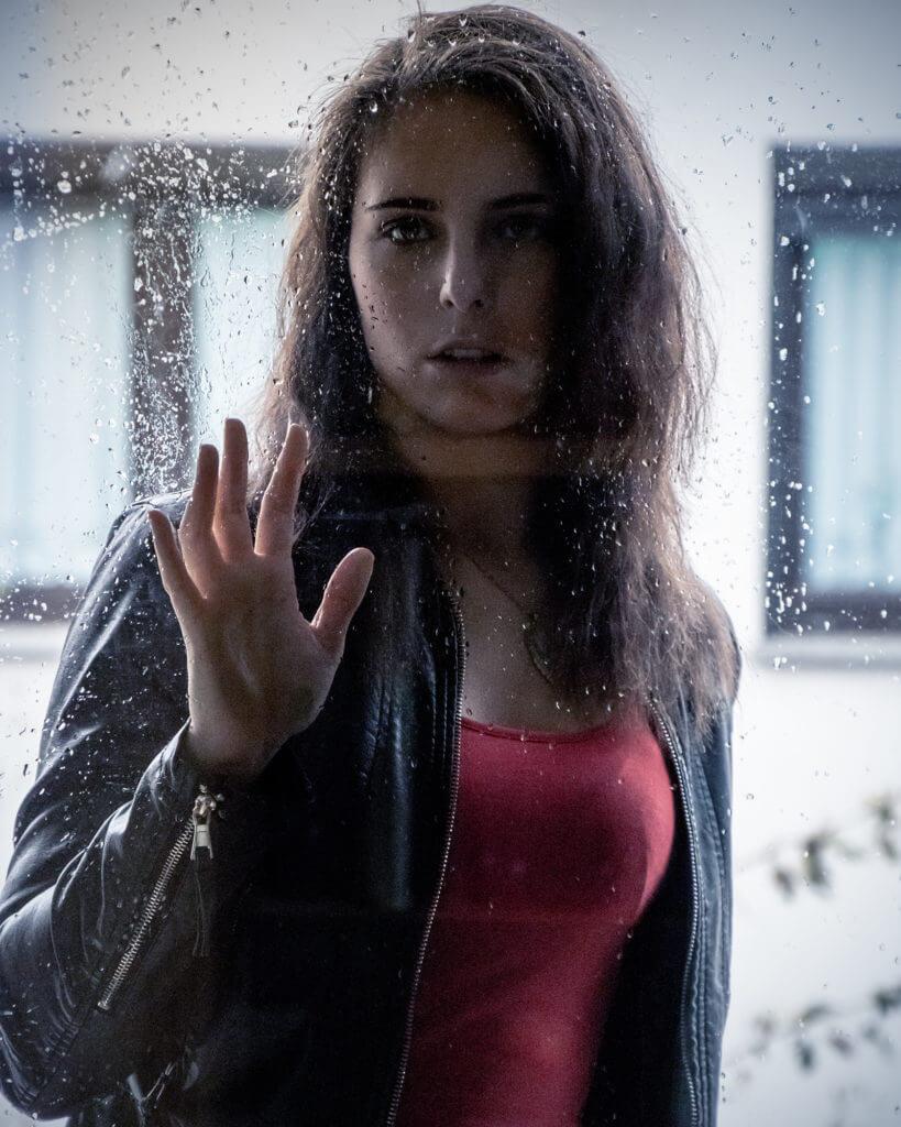 Frau vor einer nassen Scheibe mit Regentropfen, als einer der Orte für Portrait Fotografie.
