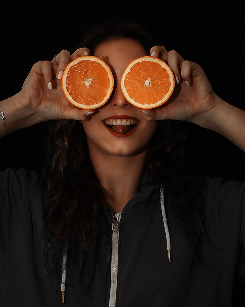 No Face Fotografie-Bild: Eine Person mit einer zerschnittenen Orange vor den Augen.