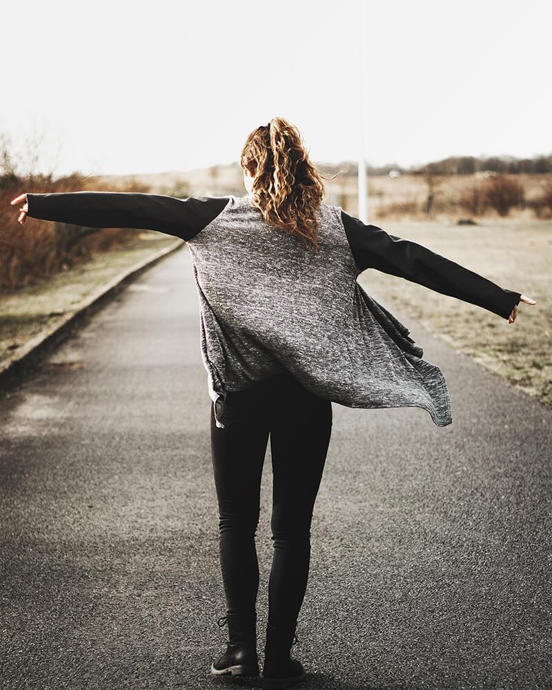 No Face Fotografie-Bild: Ein Mädchen mit ausgestreckten Armen läuft einen Weg entlang.