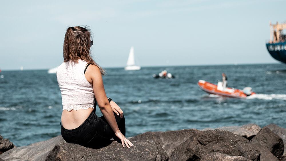 No Face Fotografie-Bild: Ein Mädchen, dass auf einer Klippe am Hafen sitzt.