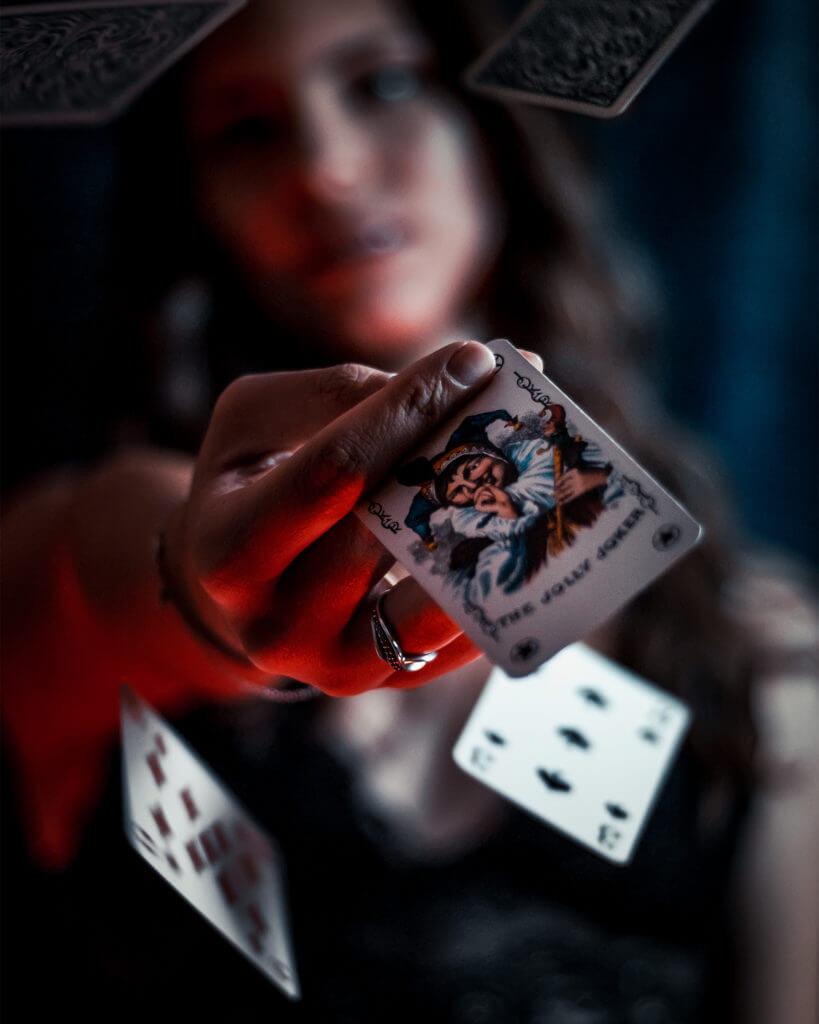 """Ein Bild aus dem Beitrag """"Portrait Ideen für Zuhause."""" Ein Model mit einer Karte in der Hand, während weitere Karten durch die Luft fliegen."""
