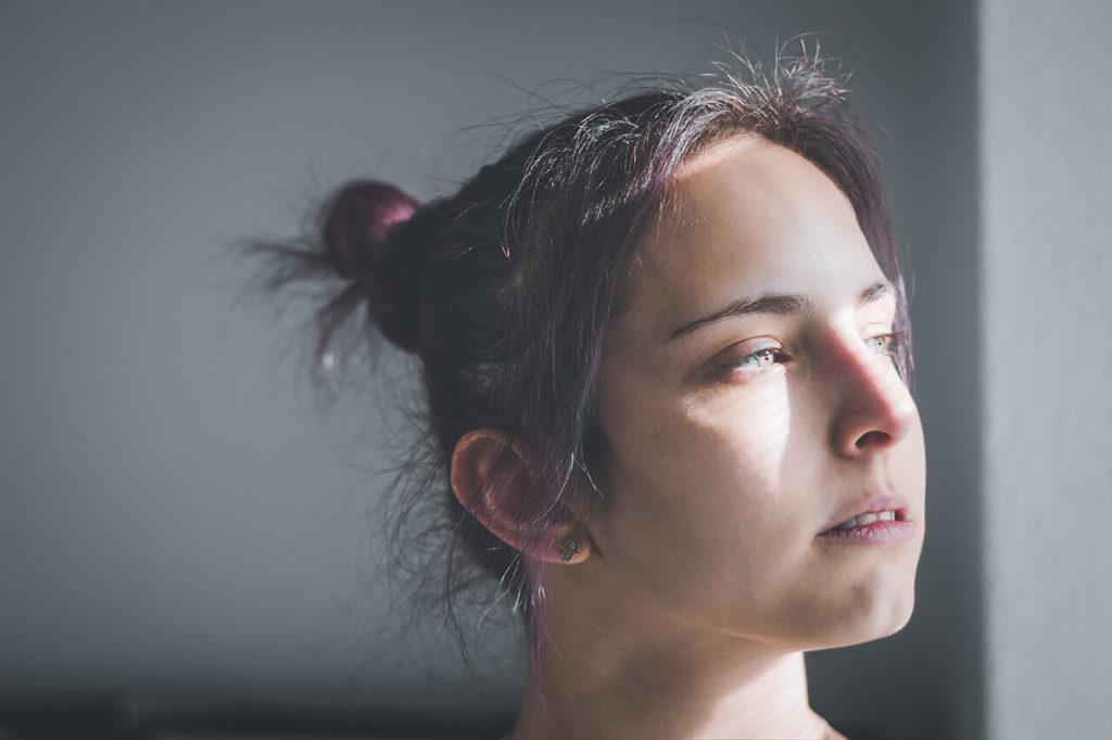 Portrait Fotografie: Frau mit Sonnenstrahlen im Gesicht