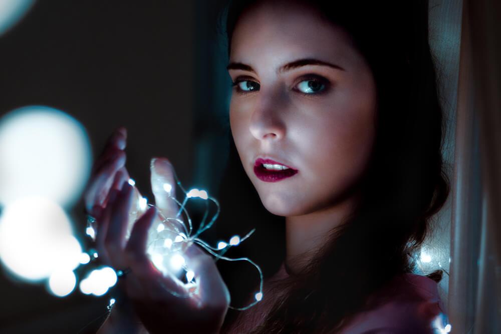 kreative Instagram Bildideen: Portrait einer Frau mit Lichterketten in der Hand